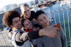 Fit and sporty team using mobile phone in the city. Royalty Free Stock Photos