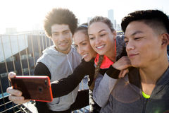 Fit and sporty team using mobile phone in the city. Stock Photo