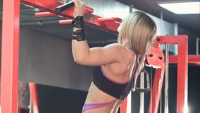 Fit sporty woman doing body lifting pull chin up exercises in gym. Professional shot in 4K resolution. 077. You can use it e.g. in your commercial video stock photos