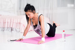 Fit sporty woman in headphones doing push ups home Royalty Free Stock Images