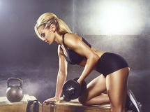 Fit and sporty young girl having a training. Underground gym. Health, sport, fitness concept. Fit and sporty young woman training in undergorund gym. Health Stock Images