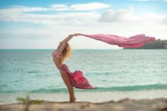 Fit and sporty young girl posing on a beach with pink flying silk stock photography