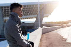 Fit and sporty young man relaxing after work out in the city. Stock Image