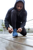 Fit and sporty young man tying her laces before a run in the cit Royalty Free Stock Photography