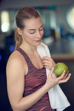 Fit sporty young woman contemplating a fresh green apple. She is holding in her hand after working out in the gym in a concept of healthy diet and active Stock Images