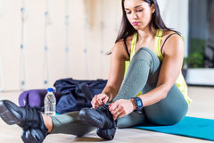 Fit sporty young woman lacing trainers shoes at. Fitness club Royalty Free Stock Photography