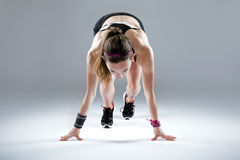 Fit and sporty young woman preparing for a run on white background. royalty free stock images