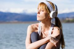 Fit and sporty young woman relaxing and listening to music after work out next to the lake. Shot of fit and sporty young woman relaxing and listening to music Royalty Free Stock Image