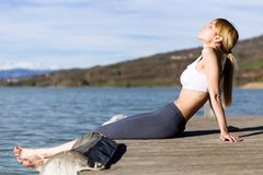 Fit and sporty young woman relaxing after work out next to the lake. Shot of fit and sporty young woman relaxing after work out next to the lake Royalty Free Stock Photo