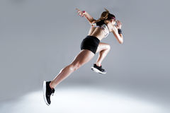 Fit and sporty young woman running on white background. stock photography