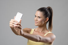 Fit sporty young woman in tank top with ponytail taking selfie photo looking at phone Stock Image