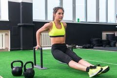 Fit strong woman doing L-sits work-out in gym, lifting up her legs, using parallel bars.  stock photos