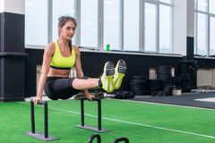 Fit strong woman doing L-sits work-out in gym, lifting up her legs, using parallel bars.  stock image