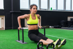 Fit strong woman doing L-sits work-out in gym, lifting up her legs, using parallel bars Stock Photos
