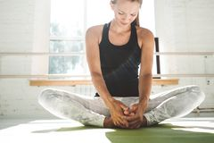 Fit strong woman doing stretching sitting on yoga mat in white gym royalty free stock image