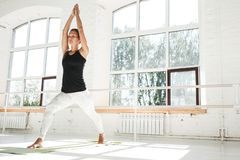 Fit strong woman doing stretching sitting on yoga mat in white gym stock photography