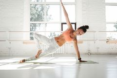 Fit strong woman doing stretching sitting on yoga mat in white gym stock photo