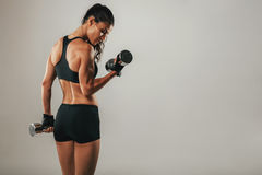 Fit strong young woman lifting weights Stock Photos