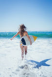 Fit surfer girl running to the sea with her surfboard Stock Image