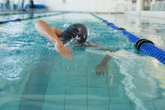 Fit swimmer doing the front stroke in the swimming pool Stock Images
