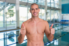 Fit swimmer gesturing thumbs up by pool at leisure center Stock Photo