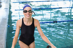 Fit swimmer smiling at camera getting out of the swimming pool Royalty Free Stock Photo