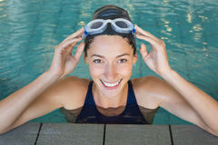 Fit swimmer smiling up at camera in the swimming pool Royalty Free Stock Image