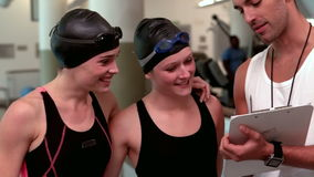 Fit swimmers discussing with trainer stock video footage