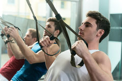 Fit thee sportsmen training body in gym. Strong young men are exercising in group. They are doing push-ups with trx straps. Men are standing and looking forward Stock Photography
