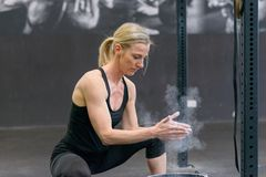Fit toned blond woman applying chalk to her hands. Fit toned blond women applying chalk to her hands from a bucket in a gym clapping to remove excess before stock image
