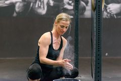 Fit toned blond woman applying chalk to her hands. Fit toned blond women applying chalk to her hands from a bucket in a gym clapping to remove excess before stock photos