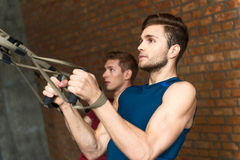 Fit two sportsmen exercising with strap Royalty Free Stock Image