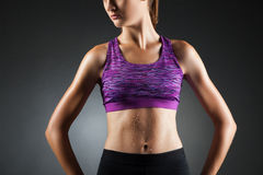 Fit unknown girl akimbo. Fit unknown sport-girl akimbo in black yoga pants and purple top. Studio portrait black background Royalty Free Stock Photo