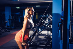 Fit woman workout triceps lifting weights in gym Royalty Free Stock Image