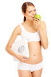 Fit woman with apple and bathroom scales Stock Photography