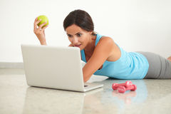 Fit woman with apple looking at computer Stock Photos