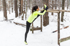 Fit woman athlete doing hamstring leg stretching exercises outdoors in woods. Female sports model exercising outdoor winter park. Royalty Free Stock Photography