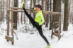 Fit woman athlete doing left leg split stretching exercises outdoors in woods. Female sports model exercising outdoor Stock Image