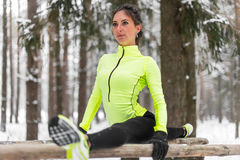 Fit woman athlete doing left leg split stretching exercises outdoors in woods. Female sports model exercising outdoor Royalty Free Stock Photos