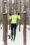 Fit woman athlete performing pull ups in a bar. Winter street outdoor training workout. Fit woman athlete performing pull ups in a bar. Winter street outdoor royalty free stock image