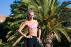 Fit woman with beautiful figure resting after active physical exercise outdoors in park Royalty Free Stock Photo