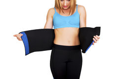 Fit woman with belt for weight loss isolated over white background Royalty Free Stock Photography