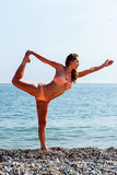 Fit woman in a bikini doing yoga at the seaside Royalty Free Stock Image
