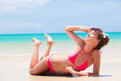 Fit woman in bikini with flower in hair on Royalty Free Stock Image