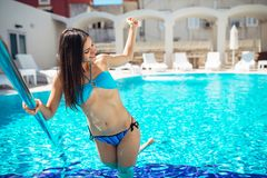 Fit woman in the bikini getting into the pool.Using hotel pool.Sunny day relaxation and leisure.Vacation fun pool party.Splashing. Water.Summer body care and Stock Photography
