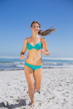 Fit woman in bikini jogging and smiling Stock Photos