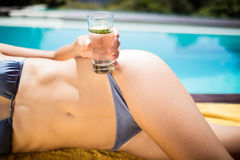Fit woman in bikini lying on towel and holding glass of water. Poolside Royalty Free Stock Photography