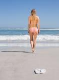 Fit woman in bikini walking towards the sea. On a sunny day Royalty Free Stock Photo