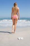 Fit woman in bikini walking towards the sea. On a sunny day Stock Image