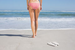 Fit woman in bikini walking towards the sea. On a sunny day Stock Images
